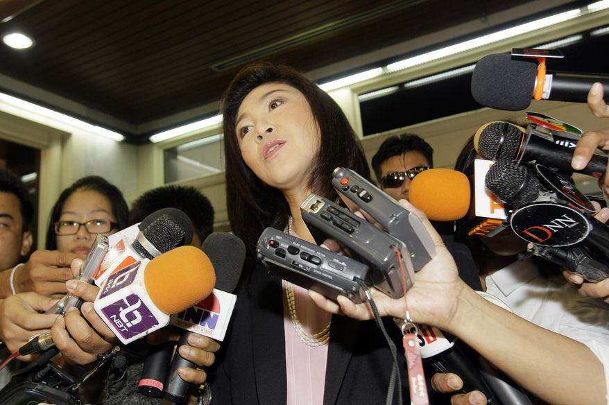 Thai prime minister-to-be Yingluck Shinawatra, center, talks with reporters after her arrival at the Pheu Thai party's headquarters in Bangkok, Thailand Wednesday, July 13, 2011. Yingluck, 44, is set to become Thailand's first female prime minister on Wednesday played down a decision by the Election Commission to postpone certification of her poll victory over allegations she violated electoral law. (AP Photo/Sakchai Lalit)