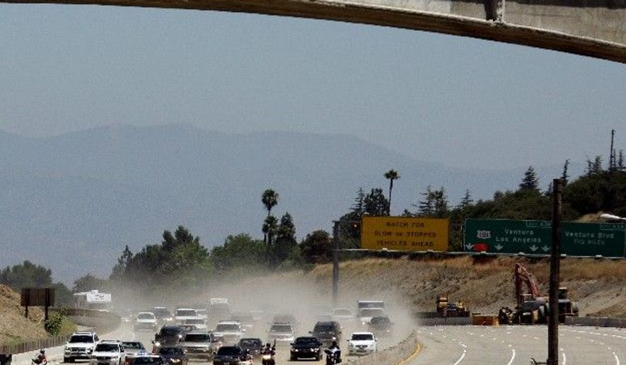 The California Highway Patrol leads the first vehicles on southbound Interstate 405 as they approach the shadow cast by the Mulholland Drive bridge (foreground) as demolition of a portion of the bridge is completed before noon in Los Angeles on Sunday. (Associated Press)