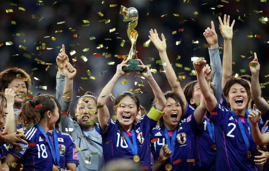 Japan celebrates with the trophy after winning its first Women's World Cup championship. Japan had not beaten the United States in their first 25 meetings. (Associated Press)
