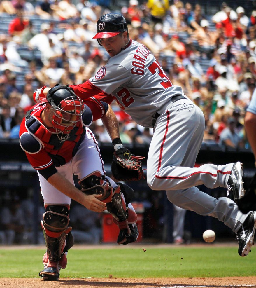 The Nationals' Tom Gorzelanny scores on Roger Bernadina's triple in the second inning, but the left-hander sprained his right ankle on the play and is listed as day to day. (Associated Press)