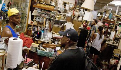 """Ruff & Ready Furnishings employee Albert McCray works the register Sunday during the store's moving sale. """"We take cards, we take cash, we take whatever we need to do to work with you,"""" Mr. McCray said. (Pratik Shah/The Washington Times)"""