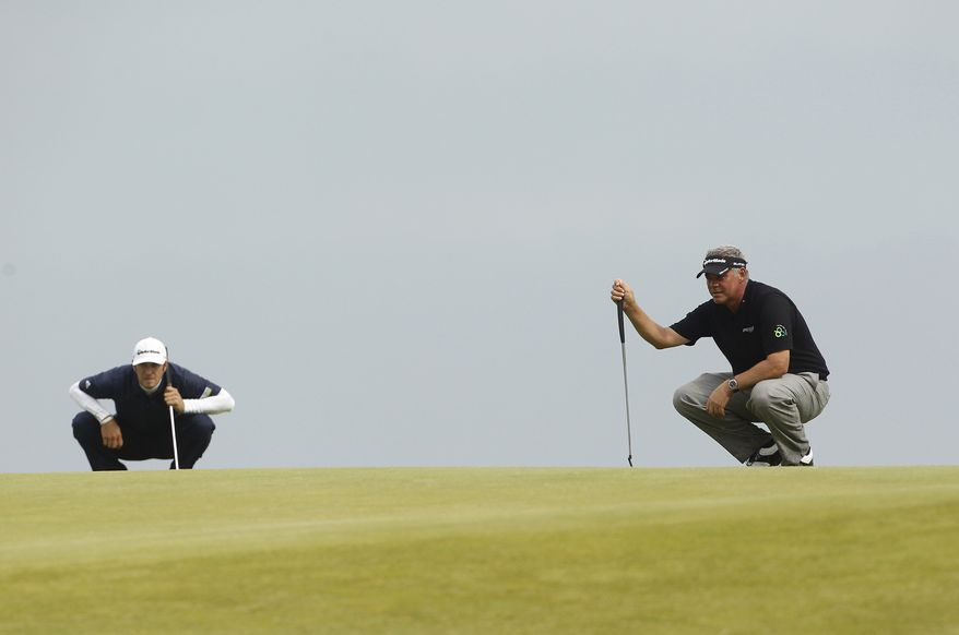 Darren Clarke (right) of Northern Ireland and Dustin Johnson of the United States line up their putts on the 10th green during the final day of the British Open Golf Championship at Royal St. George's in Sandwich, England, on Sunday, July 17, 2011. (AP Photo/Peter Morrison)