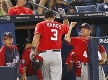 Washington Nationals' Wilson Ramos is greeted at the dugout after hitting a two-run home run in the sixth inning against the Atlanta Braves. Washington won 5-2. (AP Photo/John Bazemore)