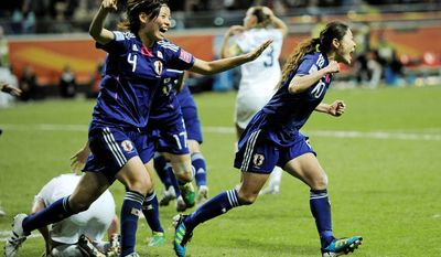 Japan's Homare Sawa and her teammate Saki Kumagai celebrate during the championship match between Japan and the United States for the Women's World Cup on Sunday, July 17, 2011, in Frankfurt, Germany. (AP Photo/Martin Meissner)