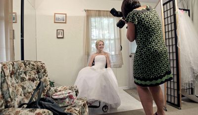 ASSOCIATED PRESS Rachelle Friedman has her photo made by wedding photographer Martha Manning during the fitting for her wedding dress in Raleigh, N.C. Miss Friedman was left paralyzed after a pool accident that postponed her wedding plans.