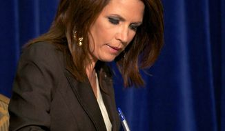 "Presidential candidate Rep. Michele Bachmann, Minnesota Republican, signs the ""cut, cap and balance"" pledge during a news conference while campaigning in Columbia, S.C., on Monday. (Associated Press)"