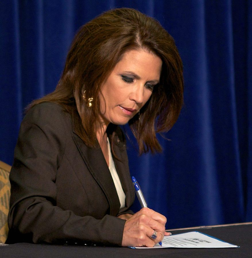 """Presidential candidate Rep. Michele Bachmann, Minnesota Republican, signs the """"cut, cap and balance"""" pledge during a news conference while campaigning in Columbia, S.C., on Monday. (Associated Press)"""