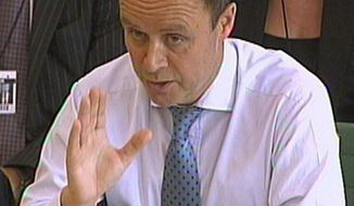 **FILE** In this photo from July 12, 2011, London's Metropolitan Police Assistant Commissioner John Yates gives evidence to a House of Commons Home Affairs Committee regarding recent phone hacking allegations. (Associated Press)