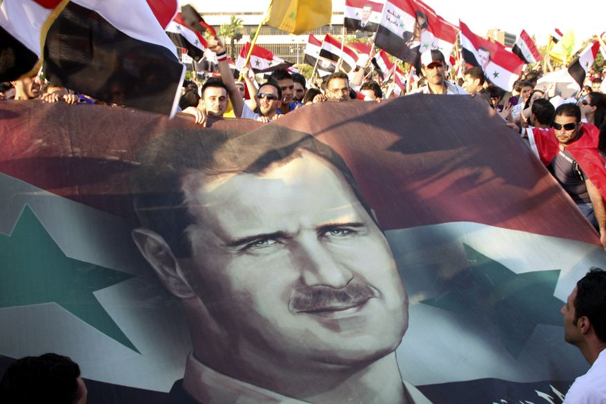 Syrians carry national flags and a picture of Syrian President Bashar Assad as they protest in support of him at the Umayyad Square in downtown Damascus, Syria, on July 17, 2011. (Associated Press)