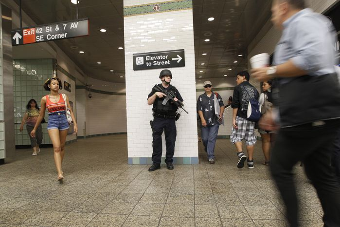 A heavily armed police officer stands guard at a Times Square subway station in New York on July 1, 2011. (Associated Press)