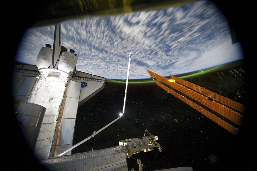 This panoramic view provided by NASA was photographed from the International Space Station, looking toward Earth past the cargo bay of the docked space shuttle Atlantis and part of the station, including a solar array panel, on Thursday, July 14, 2011, as the complex passed over the Southern Hemisphere. The Aurora Australis, or Southern Lights, can be seen on Earth's horizon, and a number of stars also are visible. (AP Photo/NASA)