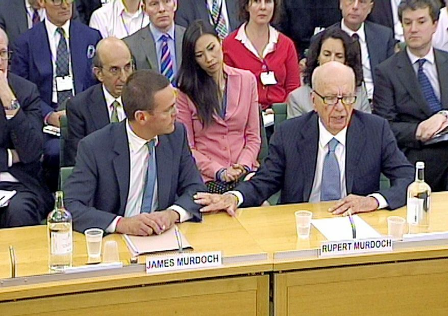 ** FILE ** James Murdoch (left) and his father, Rupert Murdoch, testify on Tuesday, July 19, 2011, before the British Parliament's Culture, Media and Sport Committee about the now-shuttered News of the World phone-hacking scandal. (Associated Press)