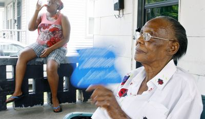 Indiana Walton, 82, cools herself on the front porch of her home in Grand Rapids, Mich., on Tuesday while her daughter, Tamara, drinks a cold soda pop. The heat poses a variety of health problems for older people. (Associated Press)