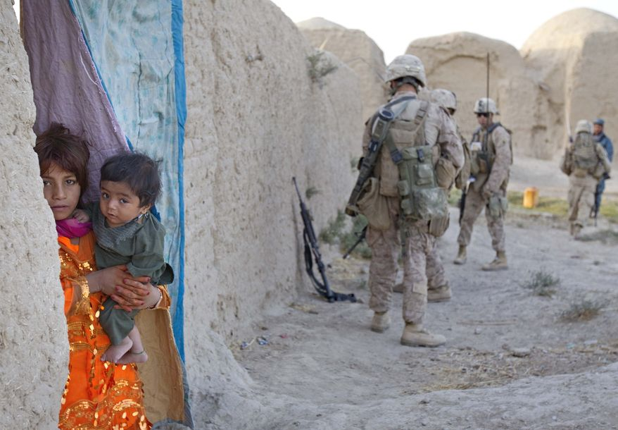 A young Afghan girl peers out from her compound as U.S. Marines with the 3rd Battalion, 2nd Marines, based at Camp Lejeune, N.C., look for insurgents in the village of Mushazi, in Afghanistan's Helmand province, on Tuesday, July 19, 2011. (AP Photo/David Goldman)