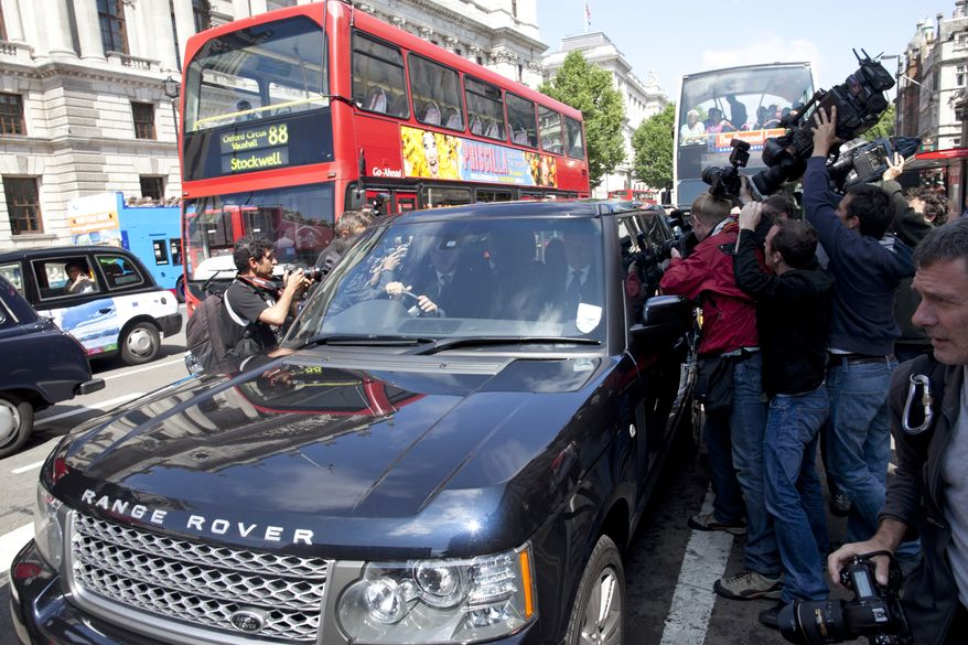 Photographers and cameramen surround the Range Rover carrying media mogul Rupert Murdoch along Whitehall in London on Tuesday, July 19, 2011, ahead of his and his son James' appearance before a House of Commons committee on the News of the World phone-hacking scandal. (AP Photo/Elizabeth Dalziel)