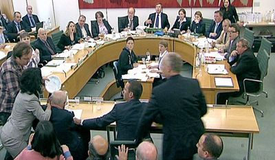 Committee members react after a protestor, left checked shirt, named on Twitter as Jonnie Marbles, tries to throw a paper plate covered in shaving foam over Rupert Murdoch as he gave evidence to a House of Commons Committee in London, Tuesday, July 19, 2011, on the News of the World phone hacking scandal. (AP Photo/pa)
