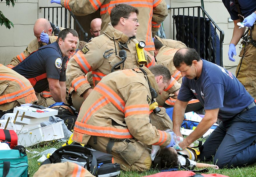 Emergency crews work to save a mother and her four children after the family was pulled from a burning house in Medford, Ore., on Monday, July 18, 2011. Authorities believe the five, all of whom died, were stabbed and suffered smoke inhalation. (AP Photo/Mail Tribune, Bob Pennell)