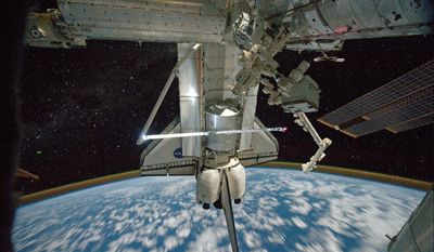 """ASSOCIATED PRESS This image provided by NASA shows a view of Space Shuttle Atlantis while still docked with the International Space Station taken by crew member Mike Fossum aboard the station Monday. The robotic arm on the shuttle appears to be saluting """"goodbye."""" Earth's airglow is seen as a thin line above Earth's horizon."""
