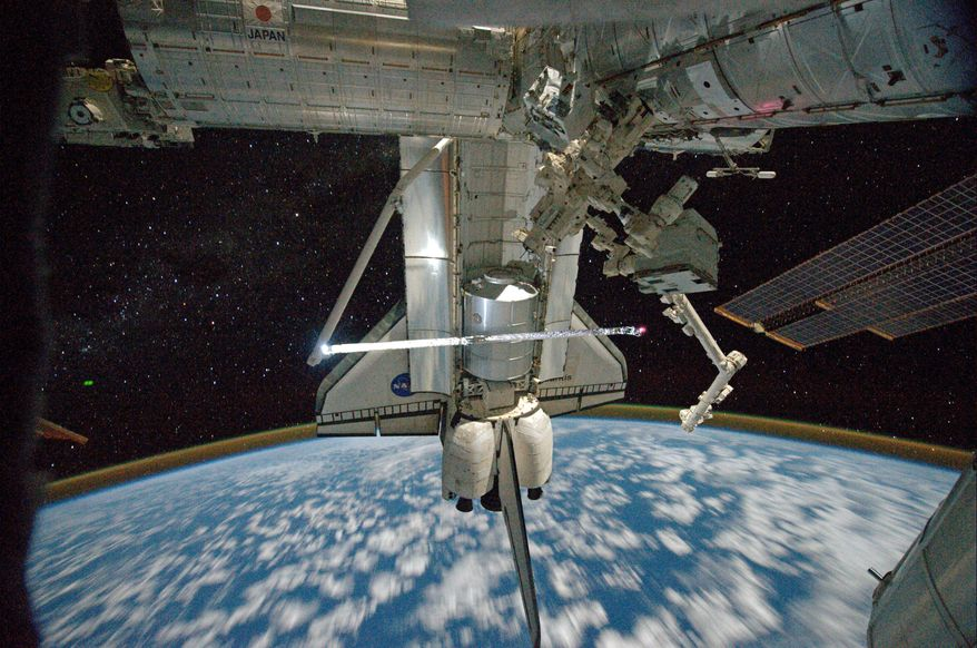 "ASSOCIATED PRESS This image provided by NASA shows a view of Space Shuttle Atlantis while still docked with the International Space Station taken by crew member Mike Fossum aboard the station Monday. The robotic arm on the shuttle appears to be saluting ""goodbye."" Earth's airglow is seen as a thin line above Earth's horizon."