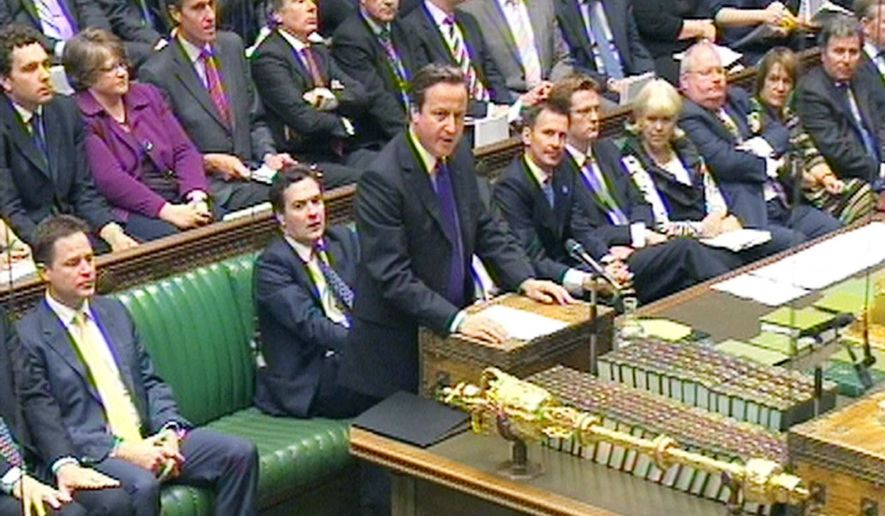 Prime Minister David Cameron (standing) answers questions in the House of Commons on Wednesday about his hiring of former News of the World editor Andy Coulson as communications director. Mr. Coulson, implicated in the newspaper phone-hacking scandal, resigned from the government job in January. (Associated Press)