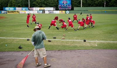 NEEDS WORK: A member of the grounds crew rakes the field while Potomac Nationals players warm up at Pfitzner Stadium. Conditions of the field have caused multiple postponements and stirred up a war of words about how bad it really is. (Drew Angerer/The Washington Times)