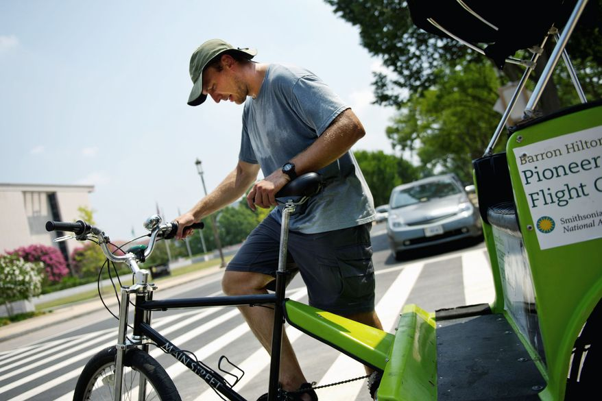 Pedicab driver Jared Denmar, of Dunn Loring, said his best method for cooling down after a ride in the Washington heat is to grab two large containers of water. (Drew Angerer/The Washington Times)