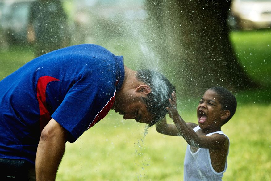 """Gabriel Carvajal of Cali, Colombia, dips his head into a sprinkler while 4-year-old Emmanuel Contreas of Boston rubs his head in Washington on Wednesday. """"The heat is never as bad as this where I live in Colombia,"""" Mr. Carvajal said. (Drew Angerer/The Washington Times)"""