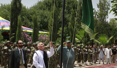 Ashraf Ghani, head of the Transition Commission raises Afghanistan's flag during the transfer of authority in Mehterlam, Laghman province, east of Kabul, Afghanistan on Tuesday, July 19, 2011. NATO handed over responsibility for the security of the capital of an eastern province to Afghan forces Tuesday, the latest step in a transition process that will lead to the withdrawal of all foreign combat troops by the end of 2014. (AP Photo/Musadeq Sadeq)