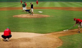 The grounds crew prepares the field for play, at Pfitzner Stadium, prior to a game between the Potomac Nationals and the Lynchburg Hillcats, in Woodbridge, Va.  (Drew Angerer/The Washington Times)