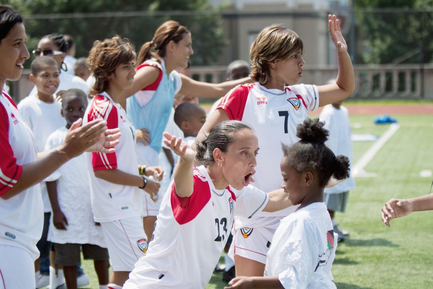 Fatiha Ouadah (23), Jalila al-Nuaimi (7) and the United Arab Emirates women's soccer team embrace children from the Boys & Girls Club of Greater Washington during a July 13 clinic in the District. (Pratik Shah/The Washington Times)