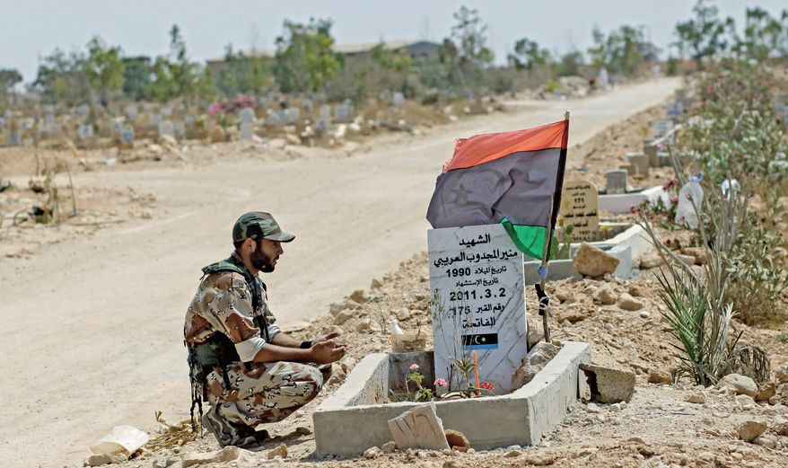 ASSOCIATED PRESS A rebel fighter visits a grave honored with a rebel flag in a cemetery in Benghazi, Libya. Rebels are seeking lethal military assistance from the U.S. to topple Col. Gadhafi's regime.