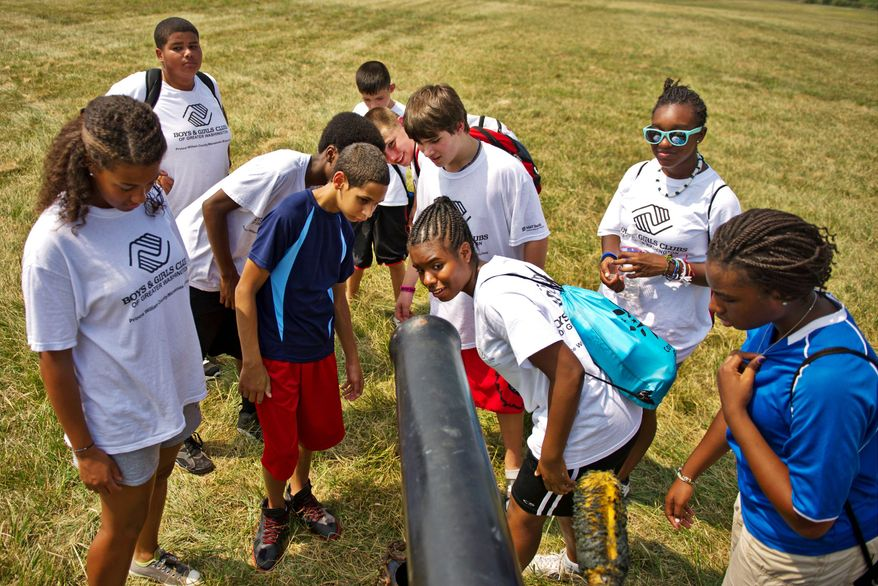 """A group of kids from the Boys and Girls Club of Prince William County take a look at a 10-pound parrot rifle at Camp Manassas on Thursday. The parrot rifle was capable of hitting targets a mile and a half away, according to Mike DeAngelo, who is a living historian camping out for the weekend. This particular cannon was used in the Civil War movie """"Gods and Generals."""""""