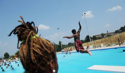 ROD LAMKEY JR./THE WASHINGTON TIMES As temperatures reach the high nineties and the heat-humidity index goes above 100 on Thursday, D.C. lifeguard Breanna Adams,18, keeps watch as youngsters keep cool at the Anacostia Pool and Recreation Center in Southeast.