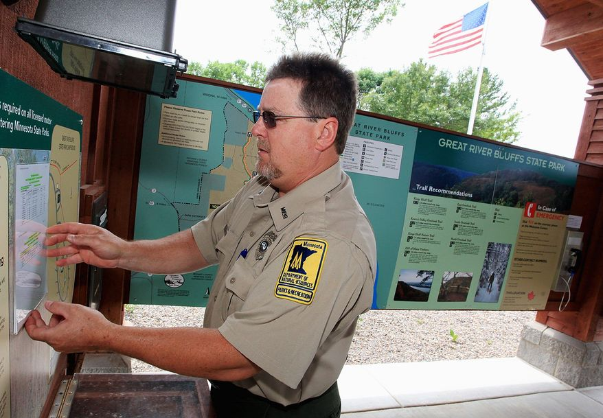 Park manager Rick Samples adjusts a camp reservation list at the Great River Bluffs State Park welcome center near Winona, Minn., on Thursday, July 21, 2011, after reopening earlier that day. Samples and his park employees have been busy re-opening the park and catching up with landscape duties because of the state shutdown. (AP Photo/Winona Daily News, Andrew Link)