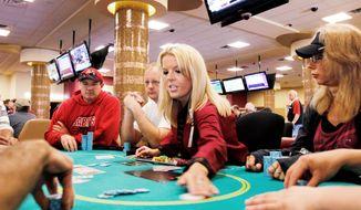 Nikki Hemstad (center), a card dealer at Canterbury Park's casino in Shakopee, Minn., is back at work Thursday after the state government shutdown ended. Despite the resolution, Minnesota made no significant progress on its budget woes, leaving it on track to face the same deficit problems in two years. (Associated Press)