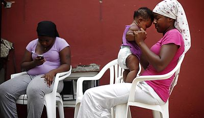 Sitting in the shade of their home Shalanda Holt, right, plays with her  daughter six-month-old Siani, as her sister Yolanda Holt reads on her mobile phone Thursday, July 21, 2011, in Philadelphia.  The National Weather Service says temperatures are expected to be near triple digits Thursday in Philadelphia, with a high of 96 degrees forecast for Pittsburgh. (AP Photo/Matt Rourke)
