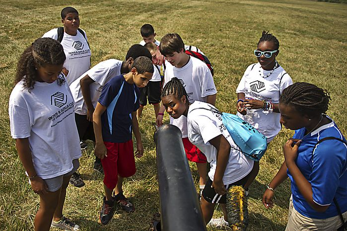 """A group of kids from the Boys and Girls Club of Prince William County take a look at a 10 pound Parrot Rifle at Camp Manassas near Jennie Dean Elementary School, in Manassas, Va., Thursday, July 21, 2011. DeAngelo and his friends were camping at Camp Manassas near Jennie Dean Elementary School and were dressed as a Confederate Artillery Unit. The Parrot Rifle was capable of hitting targets a mile and a half away, according to Mike DeAngelo, who is a living historian camping out for the weekend. This particular cannon they were using was used in the Civil War movie """"Gods and Generals."""" (Drew Angerer/The Washington Times)"""