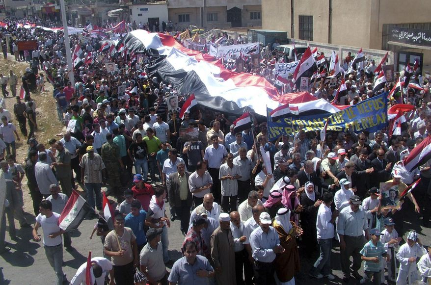 In this photo released by the official Syrian Arab News Agency (SANA), Syrian pro-government demonstrators carry national flags along with pictures of Syrian President Bashar Assad during a rally in the border town of Quneitra, about 40 miles south of Damascus, Syria, on Monday, July 18, 2011. (AP Photo/SANA)