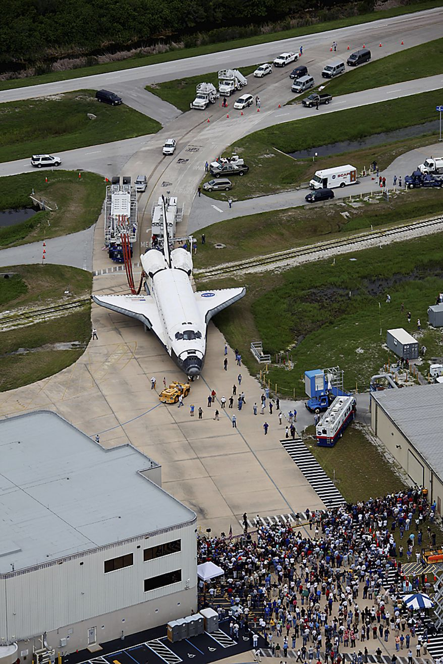Space shuttle Atlantis is towed to the Orbitor Processing Facility for decommissioning as hundreds of NASA employees gather at the Kennedy Space Center at Cape Canaveral, Fla., on Thursday, July 21, 2011. The landing of the spacecraft marks the end of NASA's 30-year shuttle program. (AP Photo/Terry Renna)