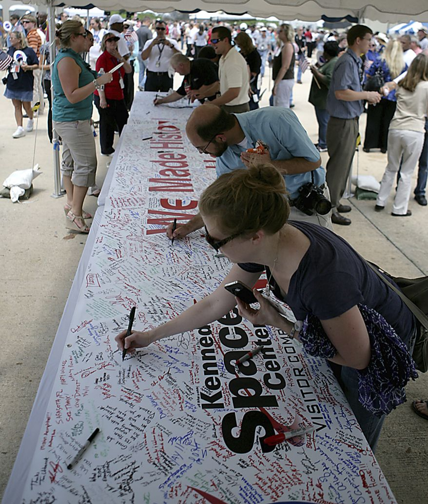 NASA employees sign a banner at the Kennedy Space Center at Cape Canaveral, Fla., on Thursday, July 21, 2011. The landing of the space shuttle Atlantis marks the end of NASA's 30-year shuttle program. (AP Photo/Dr. Scott M. Lieberman)