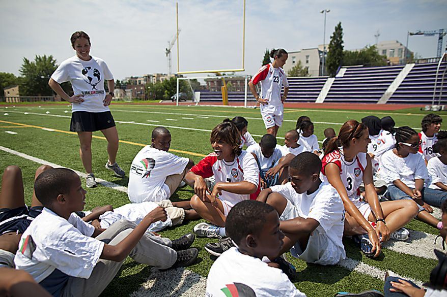 Jalila Al Nuimi, 7, of the UAE women's national soccer team, jokes around with kids from the Boys and Girls Club of Greater Washington during a soccer clinic at Cardozo High School in Northwest Washington, D.C. on Wednesday, July 13, 2011. (Pratik Shah/The Washington Times)