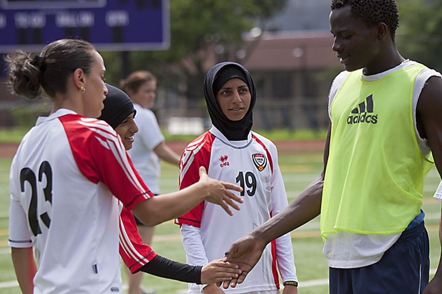 Nada Al Huwait of the UAE women's national soccer team shakes hands with an athlete from Bell Multicultural High School during a soccer clinic at Cardozo High School in Northwest Washington, D.C. on Wednesday, July 13, 2011. (Pratik Shah/The Washington Times)