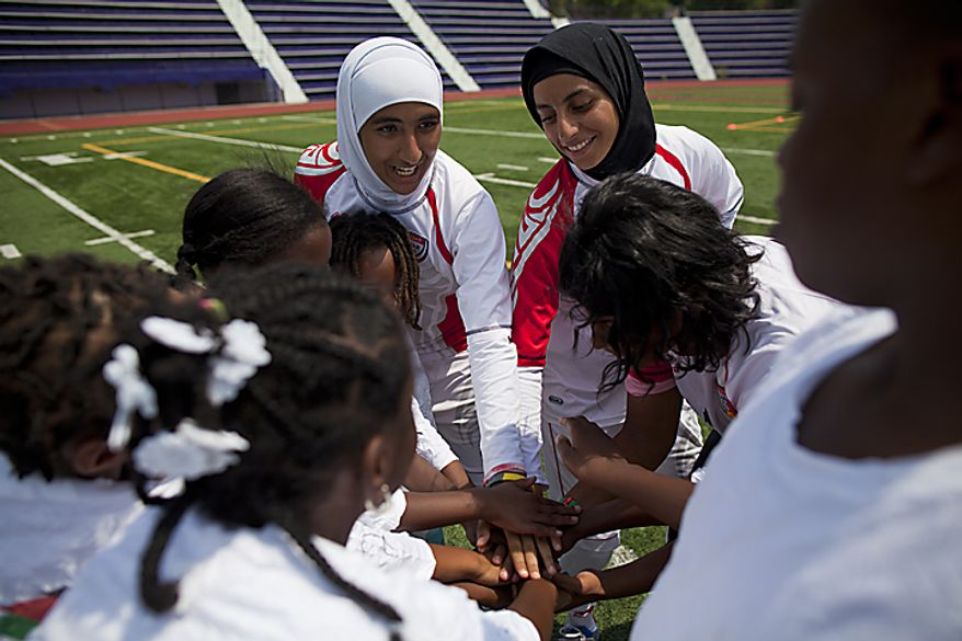 From left, Alaa Ahmed Hassan, 9, Shahad Amhed Budebs, 19, and Houriya Taheri, 1, of the UAE women's national soccer team, huddle up for a cheer with kids from the Boys and Girls Club of Greater Washington during a soccer clinic at Cardozo High School in Northwest Washington, D.C., on Wednesday, July 13, 2011. (Pratik Shah/The Washington Times)