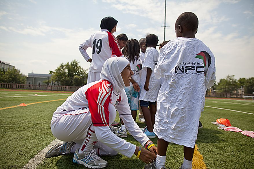 Alaa Ahmed Hassan, 9, of the UAE women's national soccer team, ties the shoe of Anthony Gent from the Boys and Girls Club of Greater Washington during a soccer clinic at Cardozo High School in Northwest Washington, D.C. on Wednesday, July 13, 2011. (Pratik Shah/The Washington Times)