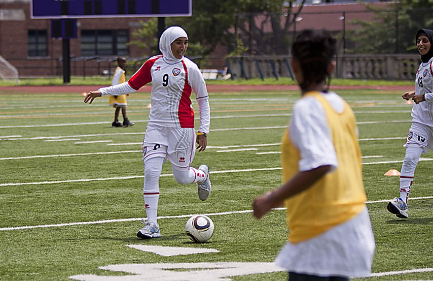 Alaa Ahmed Hassan, 9, of the UAE women's national soccer team, dribbles the ball in a mixed scrimmage with kids from the Boys and Girls Club of Greater Washington during a soccer clinic at Cardozo High School in Northwest Washington, D.C. on Wednesday, July 13, 2011. (Pratik Shah/The Washington Times)