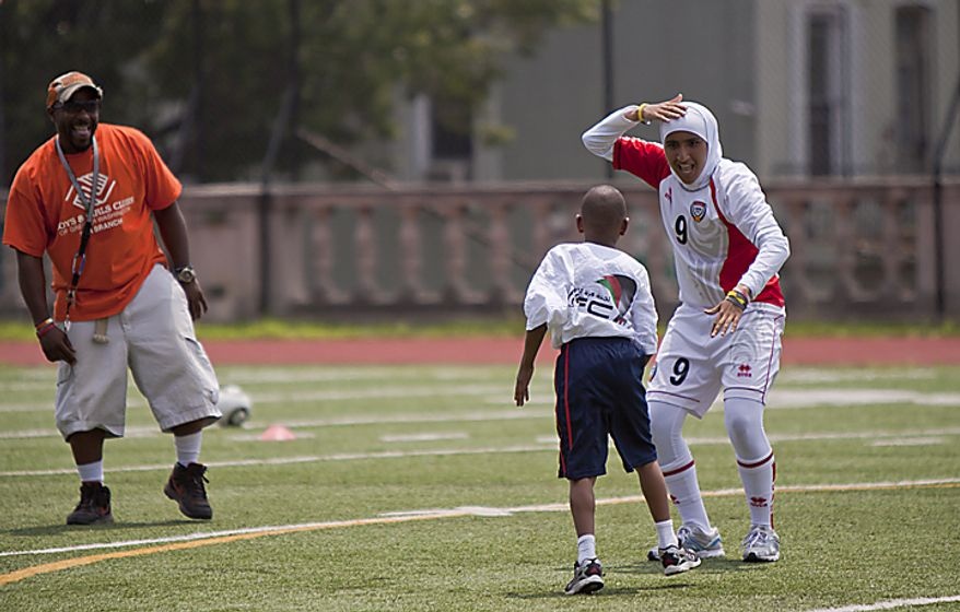 Alaa Ahmed Hassan, 9, of the UAE women's national soccer team, dances with a kid from the Boys and Girls Club of Greater Washington during a soccer clinic at Cardozo High School in Northwest Washington, D.C. on Wednesday, July 13, 2011. (Pratik Shah/The Washington Times)