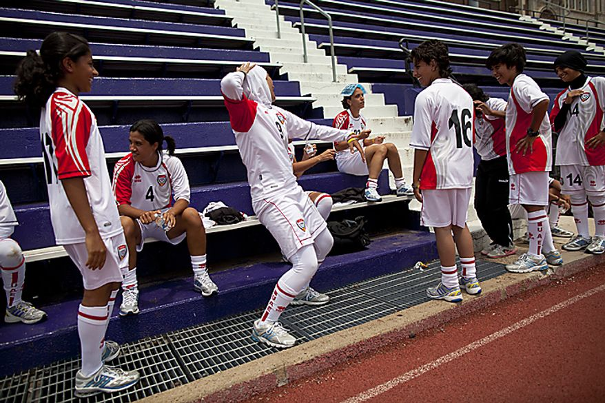 "Alaa Ahmed Hassan, 9, of the UAE women's national soccer team, shows her teammates how to dance to ""the dougie"" after kids from the Boys and Girls Club of Greater Washington showed her the dance during a soccer clinic at Cardozo High School in Northwest Washington, D.C. on Wednesday, July 13, 2011. (Pratik Shah/The Washington Times)"