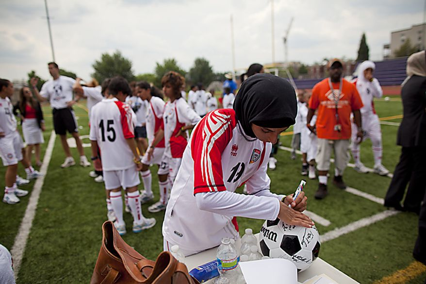Shahad Ahmed Budebs, 19, of the UAE women's national soccer team, signs a soccer ball for kids from the Boys and Girls Club of Greater Washington during a soccer clinic at Cardozo High School in Northwest Washington, D.C. on Wednesday, July 13, 2011. (Pratik Shah/The Washington Times)