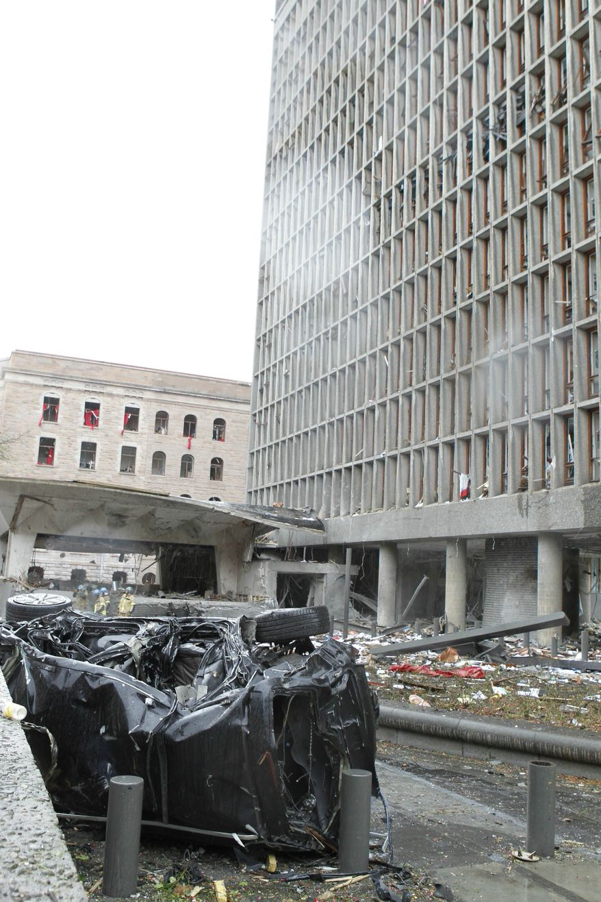 The wreckage of a car lies outside a building in the centre of Oslo, Friday, July 22, 2011, following an explosion that tore open several buildings including the prime minister's office, shattering windows and covering the street with documents. (AP Photo/Roald Berit, Scanpix, Norway)