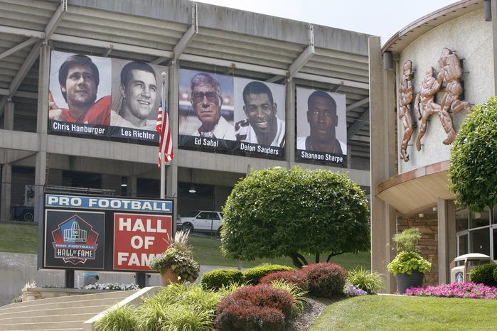 Banners featuring the Class of 2011 hang outside of Fawcett Stadium adjacent to the football museum at the Pro Football Hall of Fame, Friday, July 22, 2011, in Canton, Ohio. Although the NFL announced Thursday, July 21, the cancellation of the annual Hall of Fame Game between the Chicago Bears and the St. Louis Rams, the enshrinement will go ahead as planned. Deion Sanders, Chris Hanburger, Les Richter, Ed Sabol, Shannon Sharpe, Richard Dent, and Marshall Faulk represent the Class of 2011 who will be enshrined on Aug. 6, 2011. (AP Photo/The Repository, Scott Heckel)